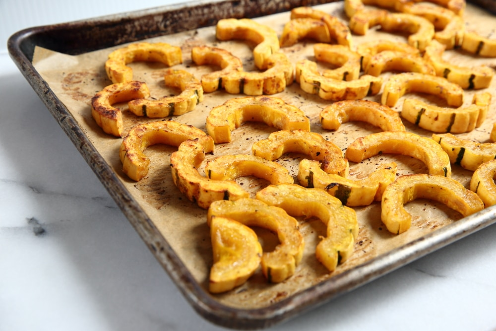 Roasted Delicata squash rings on a baking sheet.