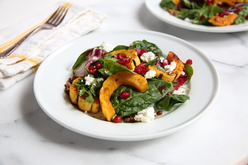 Roasted squash salad on a plate with fork in the background.