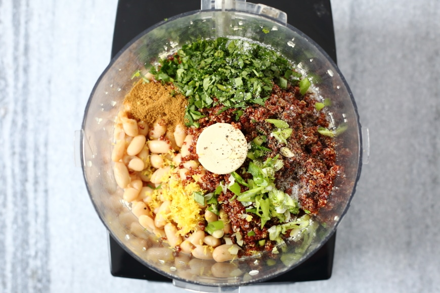 Process shot showing the ingredients for the vegan quinoa burger recipe in a food processor (not chopped).