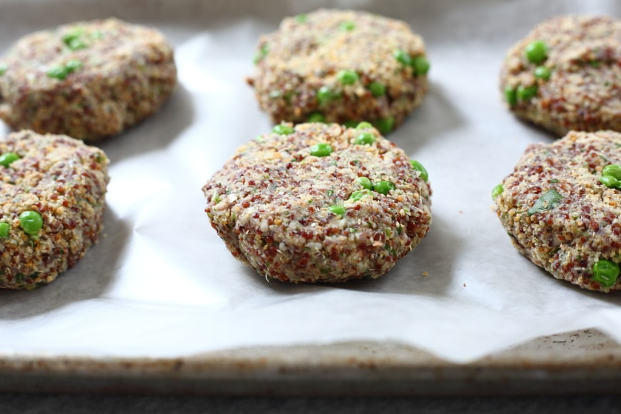 Process shot showing uncooked quinoa burger patties lined up on baking sheet.