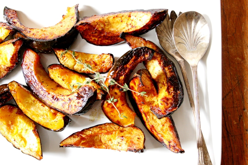 Roasted acorn squash wedges on a serving platter.