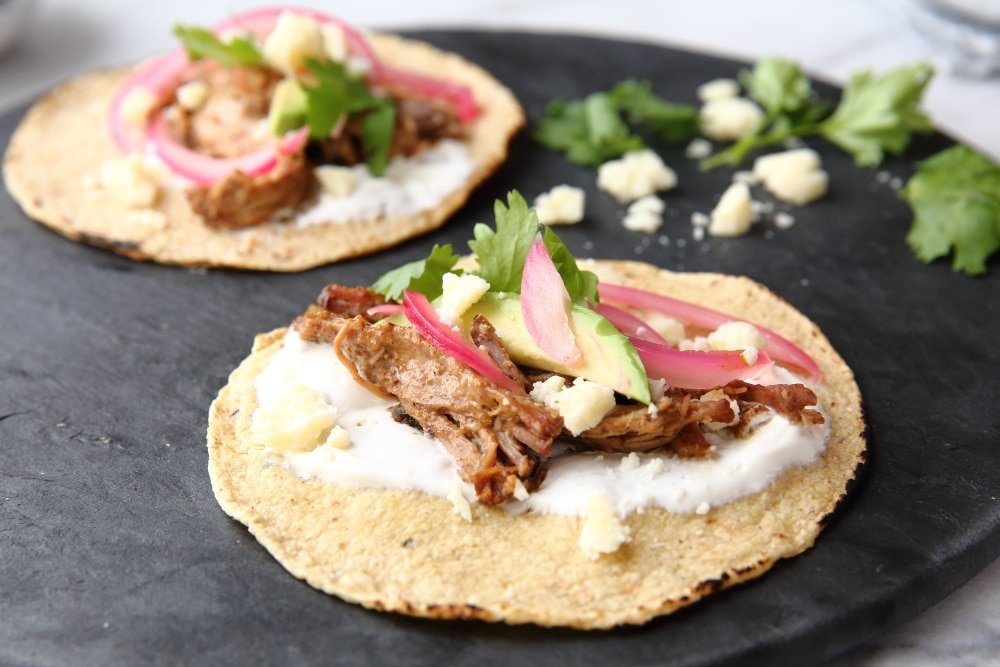 Close up of a slow cooker carnitas taco on a plate.