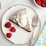 Gluten free chocolate cake on plate with whipped cream and raspberries