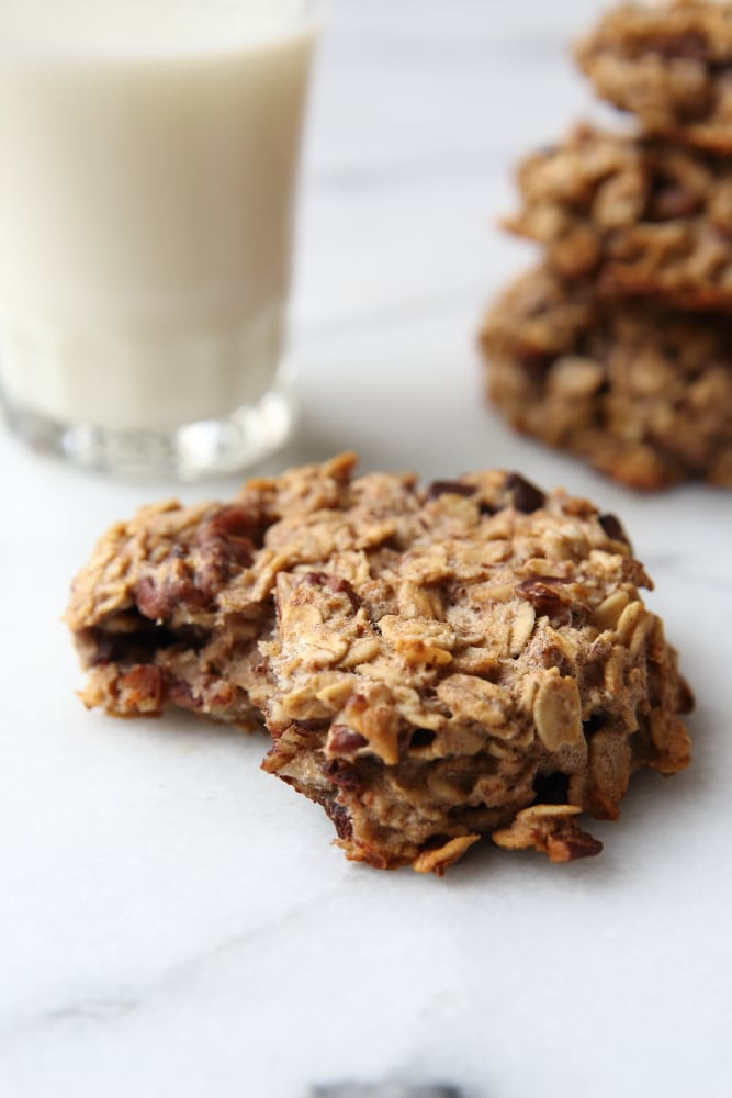 Close up of a banana breakfast cookie with a glass of milk in the background.