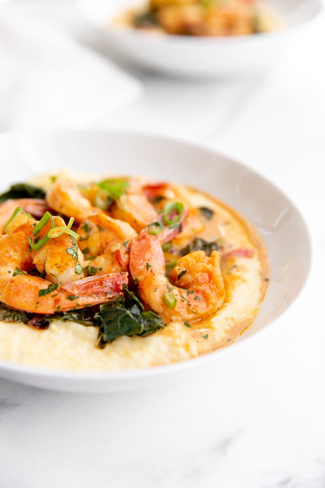 Coconut sriracha shrimp and kale over grits in serving bowl