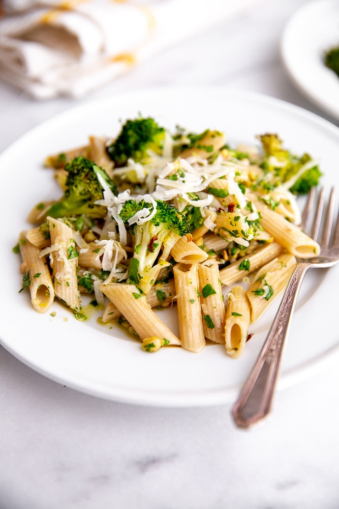 Broccoli pasta on plate with fork and napkin in background