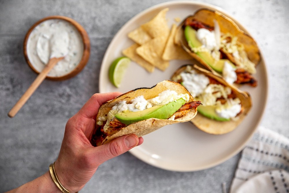 Easy chipotle chicken taco in a hand, with a plate in the background