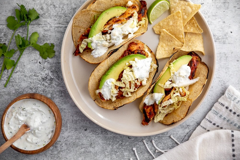 Easy chipotle chicken recipe in tacos on a plate with tortilla chips and lime crema sauce on the side