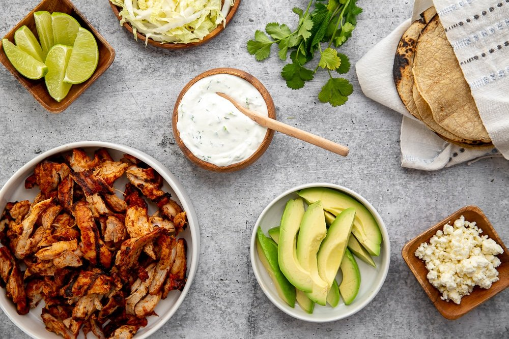 Ingredients to build easy chipotle chicken tacos on counter