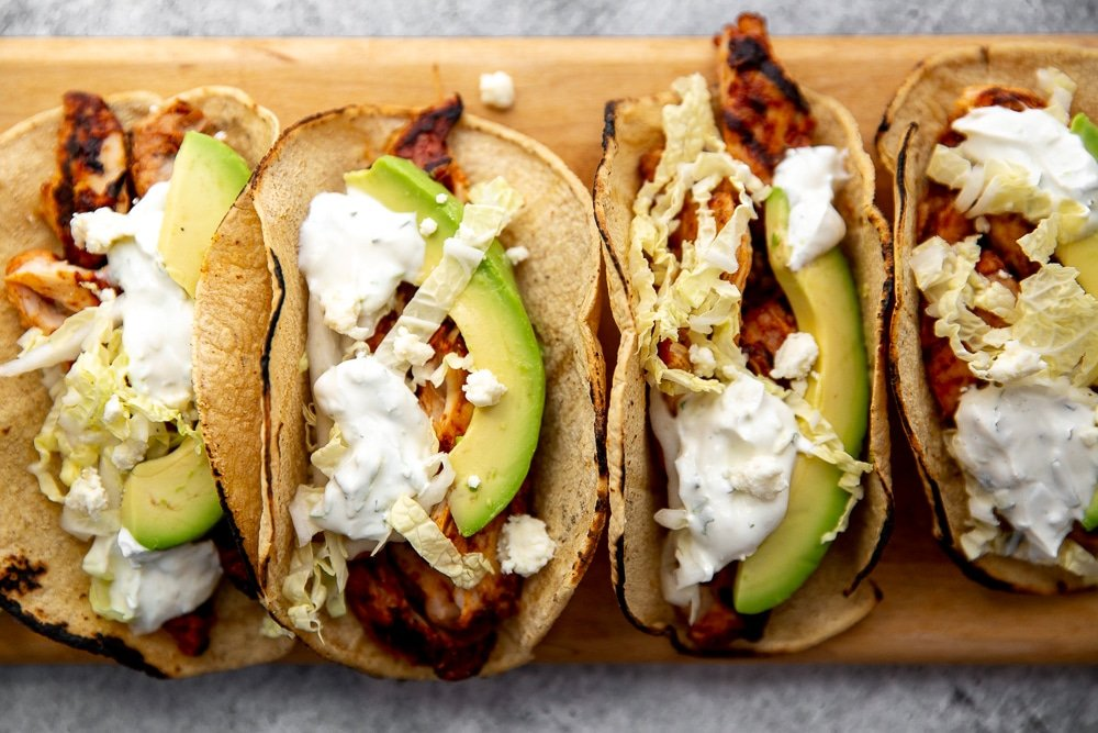 Easy chipotle chicken recipe in tacos on cutting board