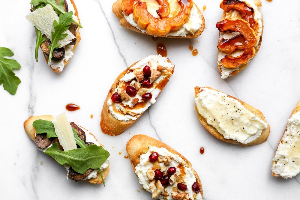 Assortment of whipped ricotta crostini on countertop