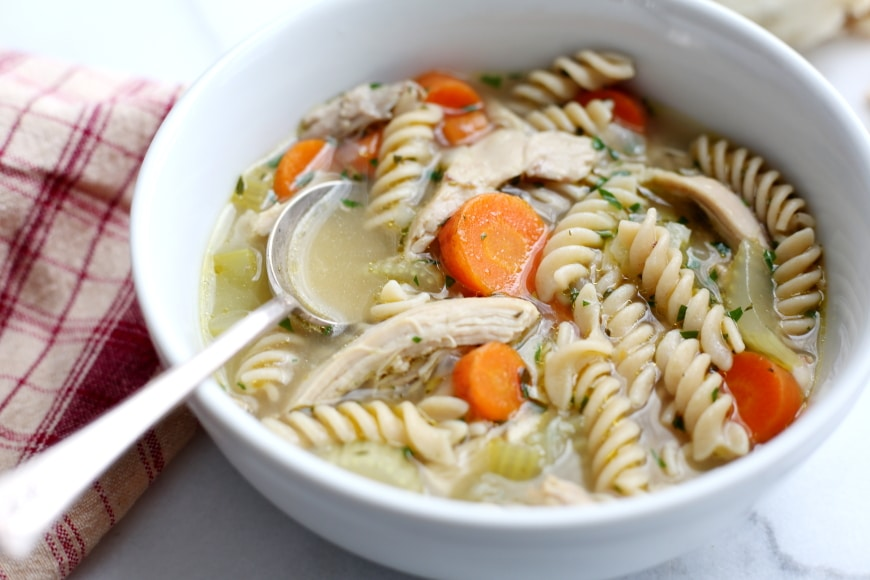 Close up of a bowl of chicken noodle soup with a spoon.