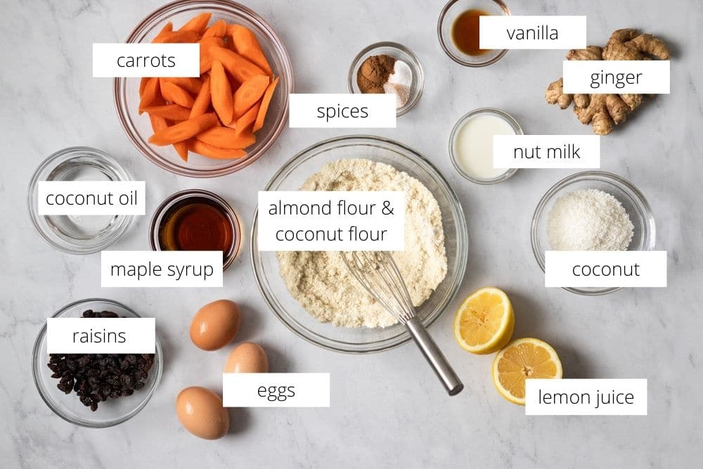 All of the ingredients for the carrot cake muffins arranged on a work surface and labeled.