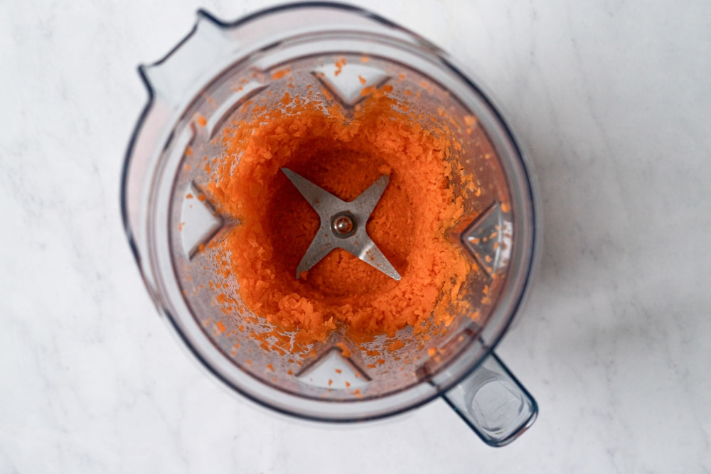 Process shot showing chopped carrots in a Vitamix blender.