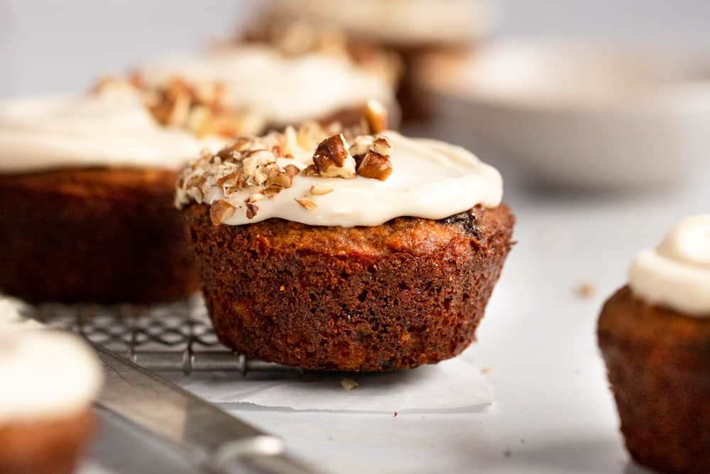 Close up of a carrot cake muffin topped with cream cheese frosting and chopped pecans.