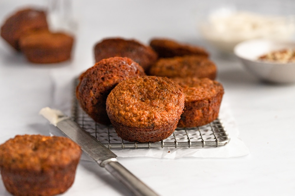 Paleo carrot cake muffins on a cooling rack.
