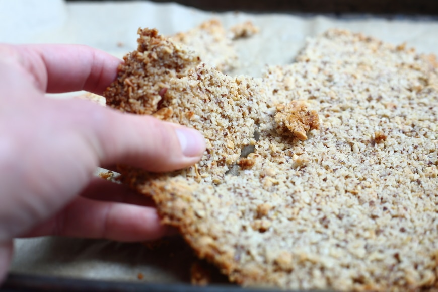 Close-up of a hand breaking the coconut peanut crumble into chunks.