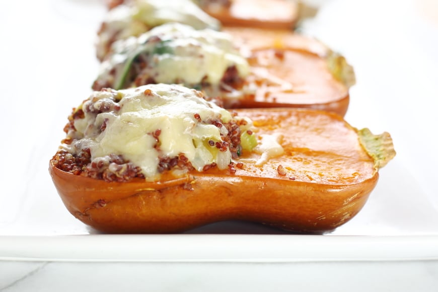 Close up side view of a stuffed honeynut squash with melted cheese.