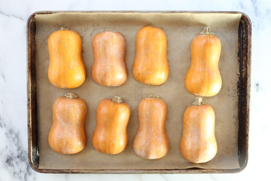Halved honeynut squash lined up on a baking sheet