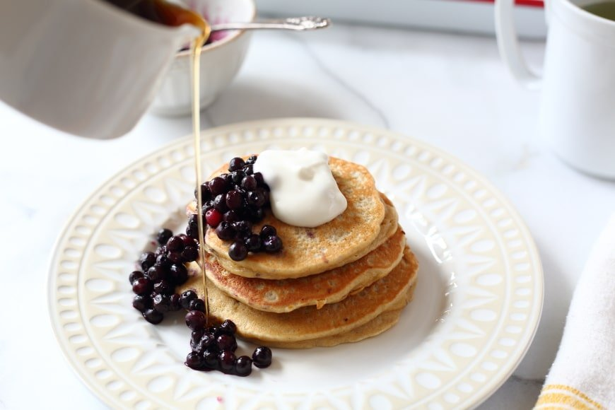 Banana oat blender pancakes on plate with syrup and berries