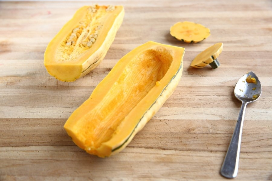 A halved delicata squash on a cutting board with a spoon for scraping out the seeds.