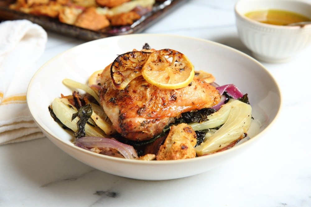 Sheet pan chicken thighs in bowl with warm panzanella salad