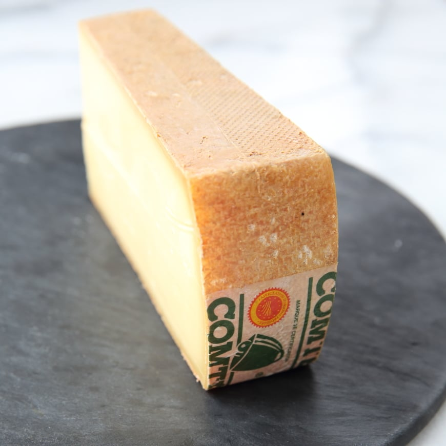 Close up of a wedge of Comté cheese.
