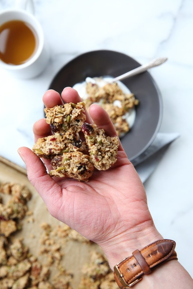 granola clusters recipe in hand with bowl in background