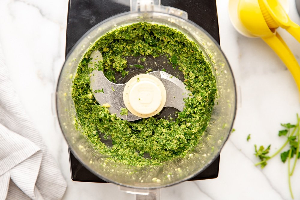 Process shot showing green sauce ingredients chopped up in food processor