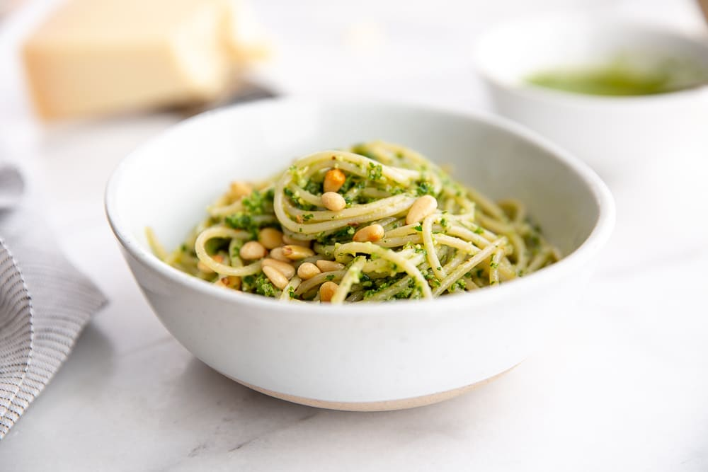 Green sauce tossed with pasta in bowl with parmesan cheese in background
