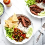 Steak burrito bowls with skirt steak, vegetables, romaine lettuce, tortilla chips and avocado crema sauce over rice.