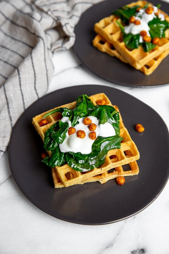 Chickpea waffles on plates, topped with sautéed spinach, yogurt and crispy chickpeas