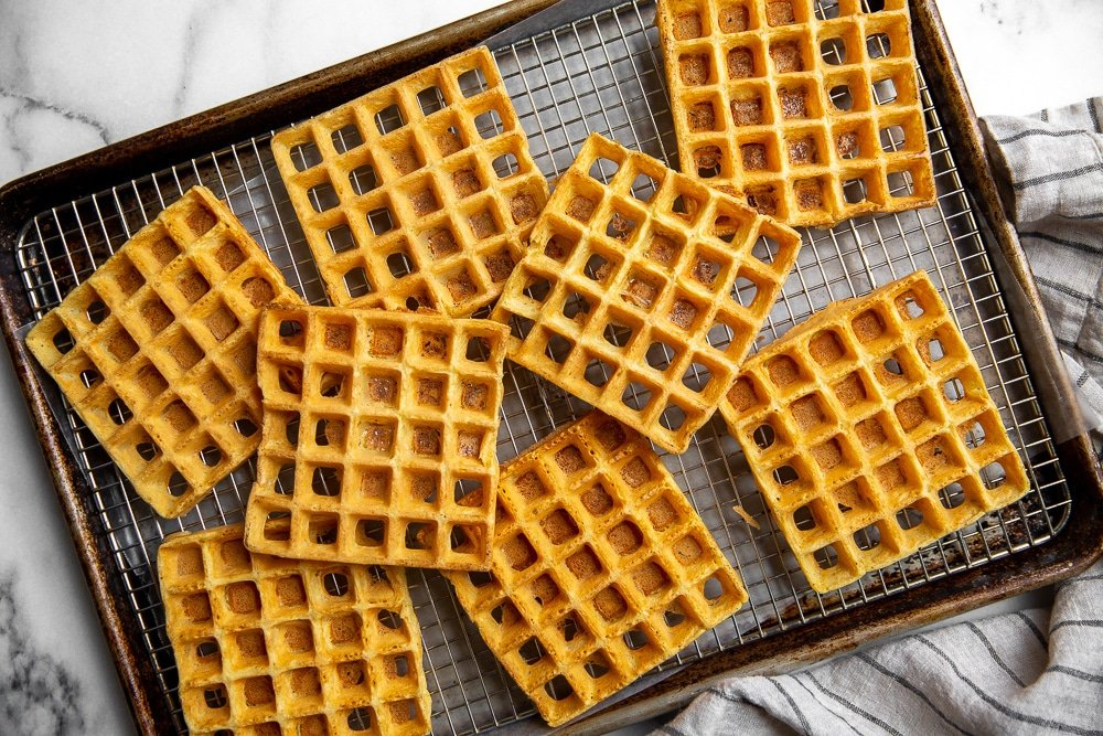 Chickpea waffles spread out to cool on rack over a baking sheet