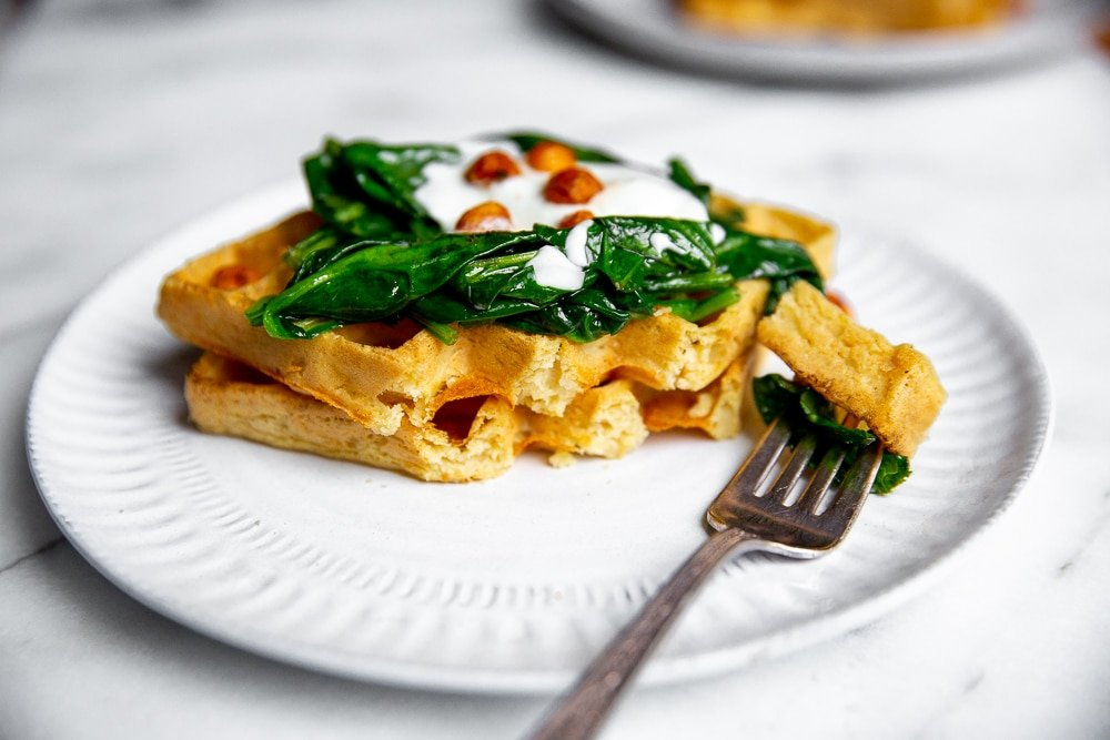 Chickpea waffles on plate with sautéed spinach, yogurt and crispy chickpeas, with fork taking a bite