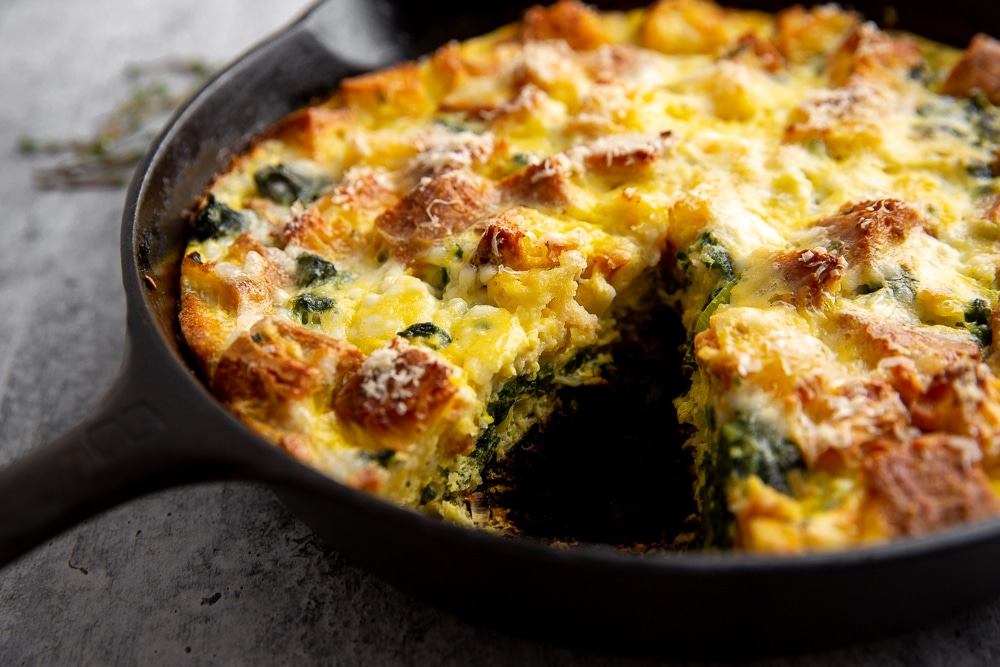 Vegetarian breakfast strata in pan with wedge removed