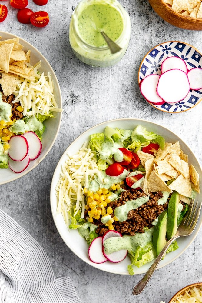 Healthy taco salad in bowl, with toppings alongside, including shredded cheddar cheese, radishes, tomatoes, tortilla chips and creamy cilantro lime dressing