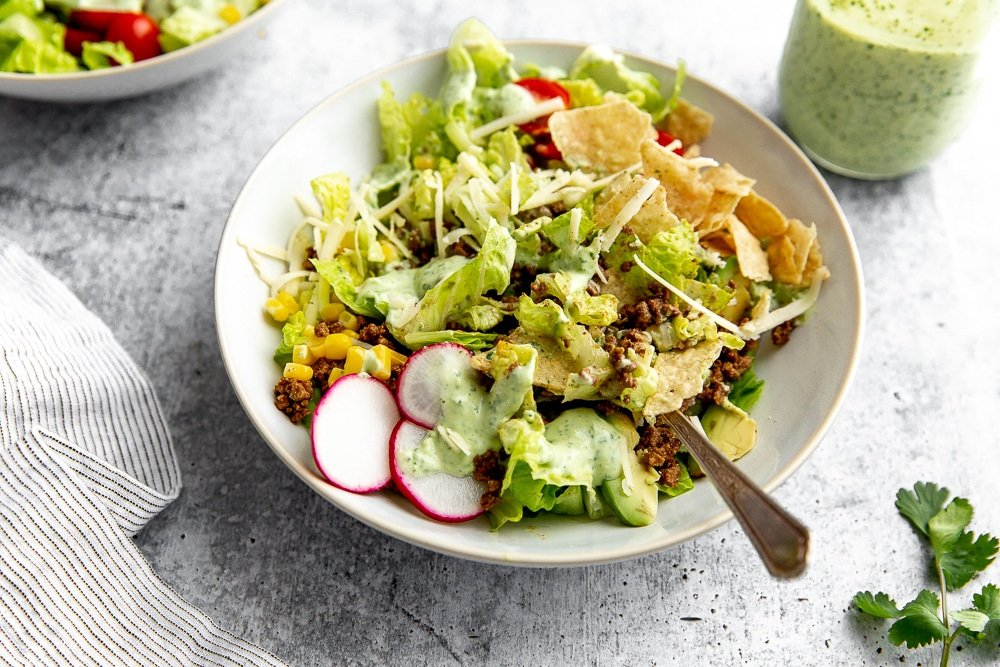 Healthy taco salad tossed in bowl with fork, with creamy cilantro lime dressing on the side