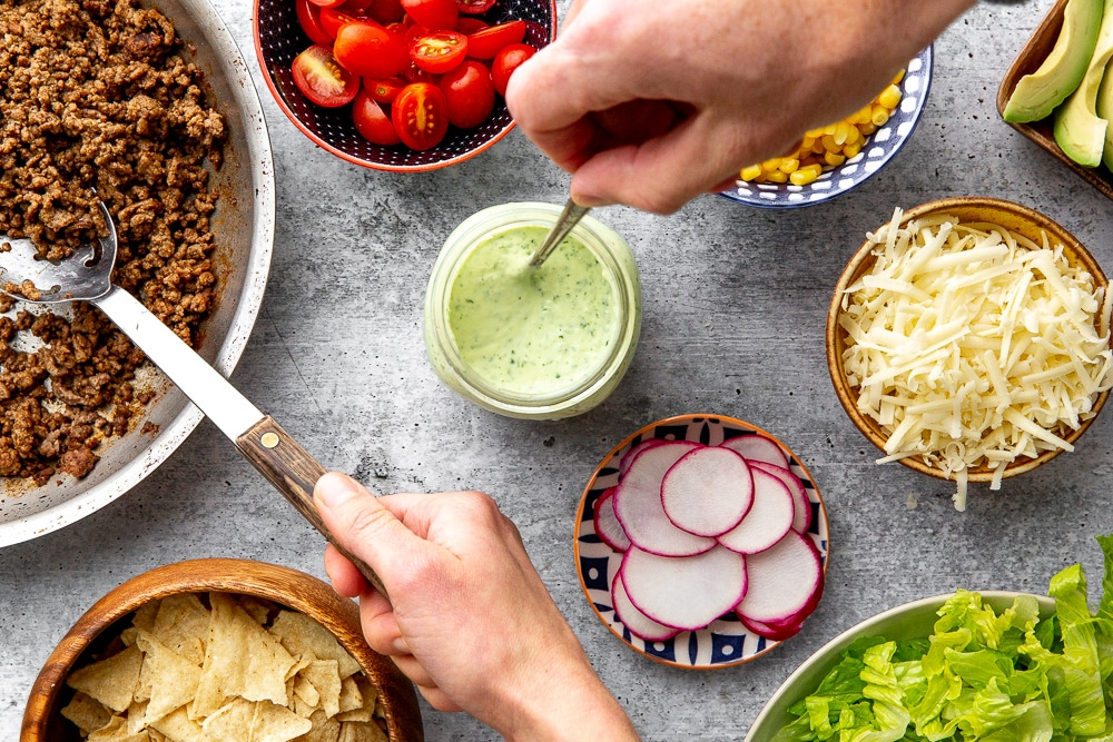 Healthy taco salad toppings arranged in bowls on counter, with hands reaching for spoons