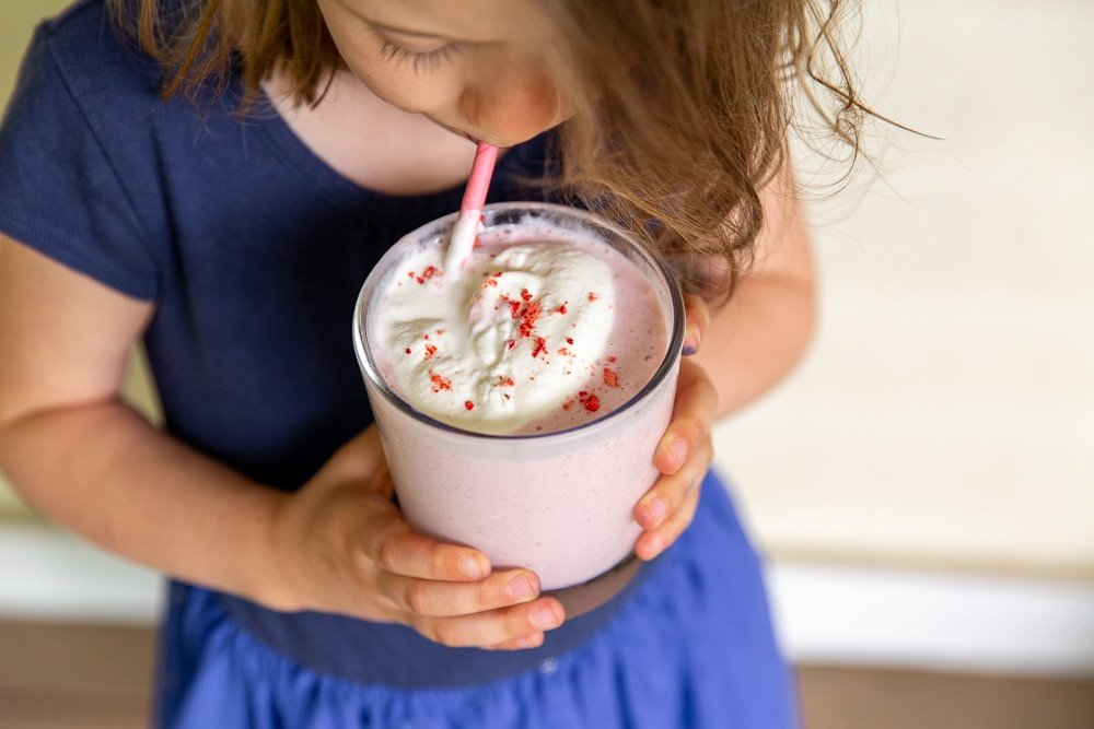 Child drinking strawberry smoothie from a glass with a straw