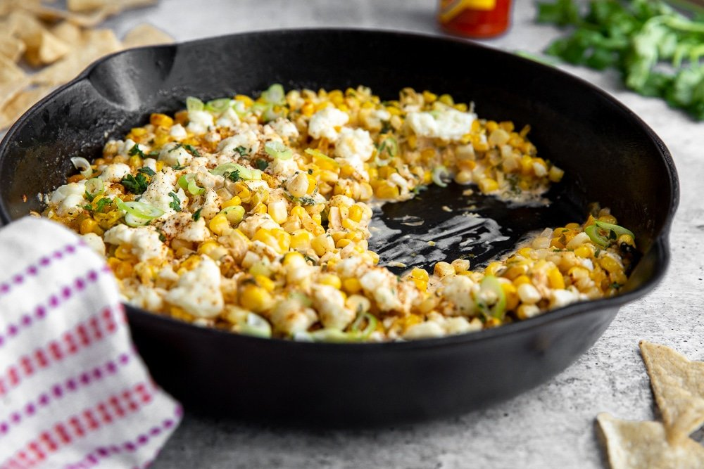 Side angle shot of Mexican street corn dip in cast iron skillet.