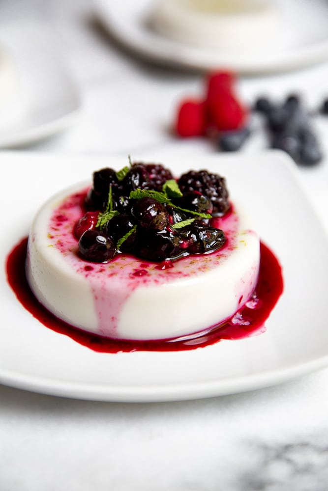 Close up side-view of panna cotta on plate, topped with roasted berries.