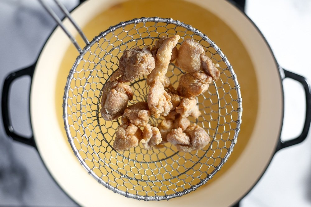 Fried chicken in a strainer coming out of the oil.