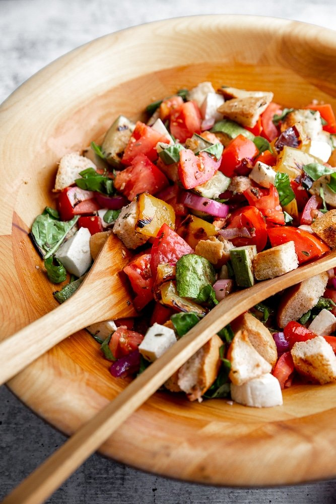 Close-up side view of panzanella salad in a large wooden salad bowl.