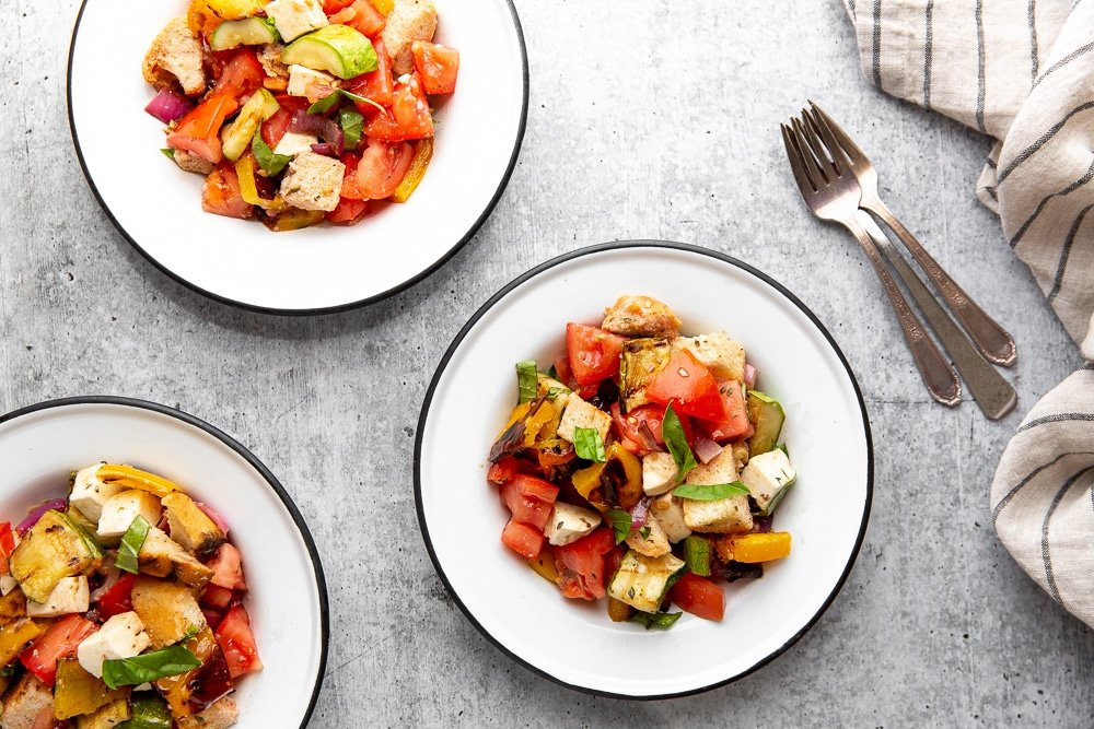 Overhead shot of three bowls of panzanella salad on a table.