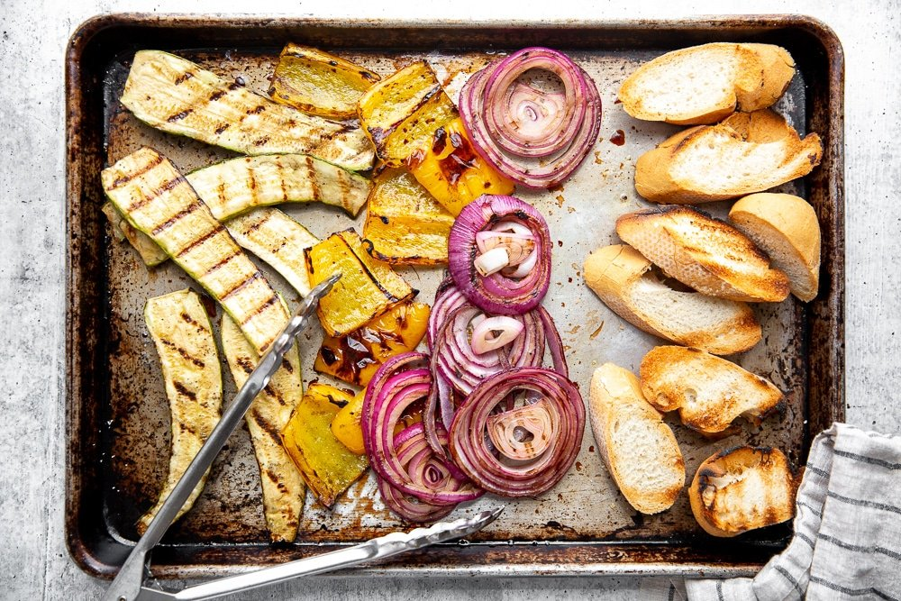 Process shot showing grilled vegetables and bread spread out on a sheet pan.