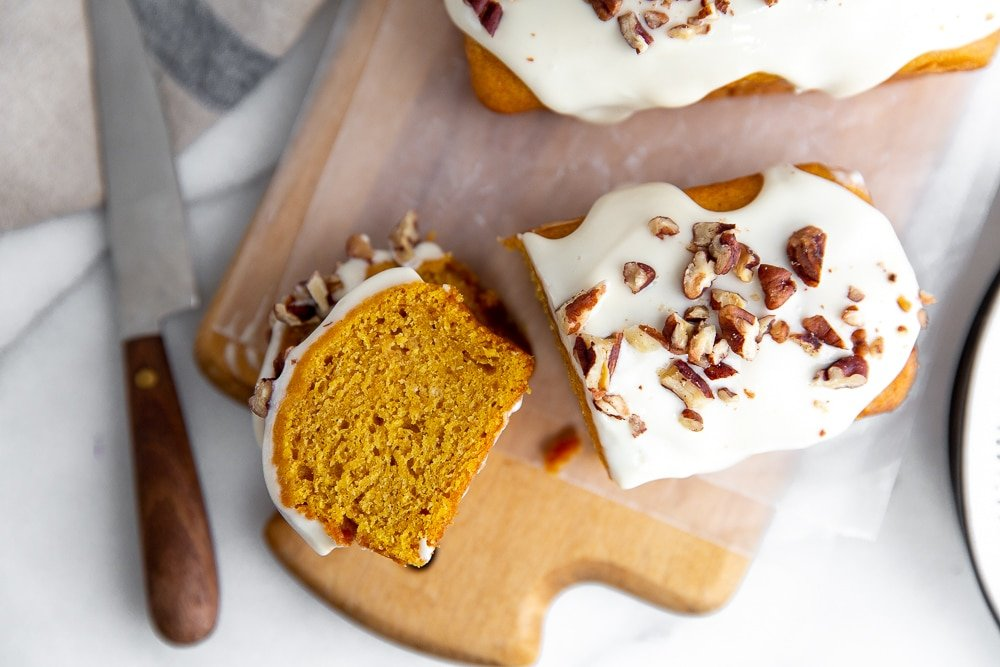 Overhead shot of a slice of pumpkin pound cake with cream cheese glaze on a wooden serving board.