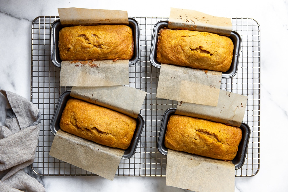 Four mini pumpkin pound cakes in baking pans on a cooling rack.