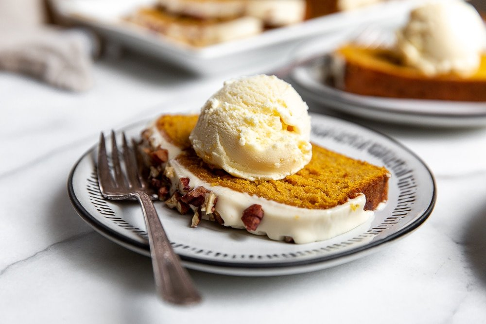 A slice of gluten free pumpkin pound cake on a plate topped with a scoop of ice cream.