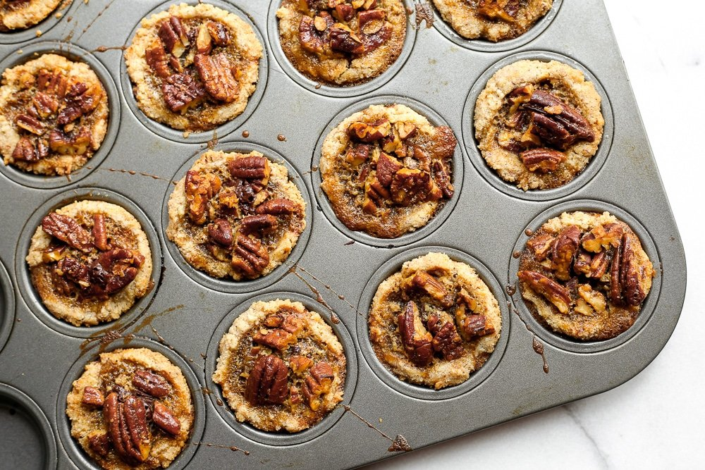 Overhead shot of gluten free pecan tarts in a mini muffin tin.