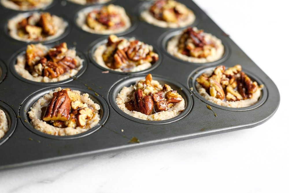 Close up of unbaked pecan tarts in the muffin tin.